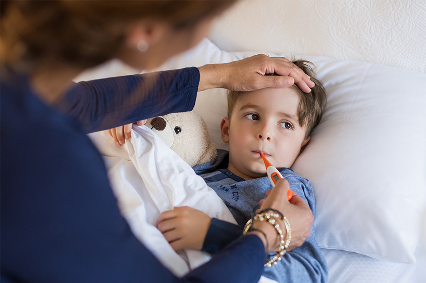 little boy in bed getting temperature checked with thermometer by his Mum